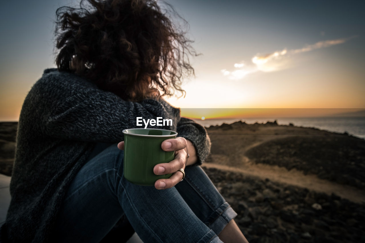 Woman Looking At View And Holding Cup Of Coffee