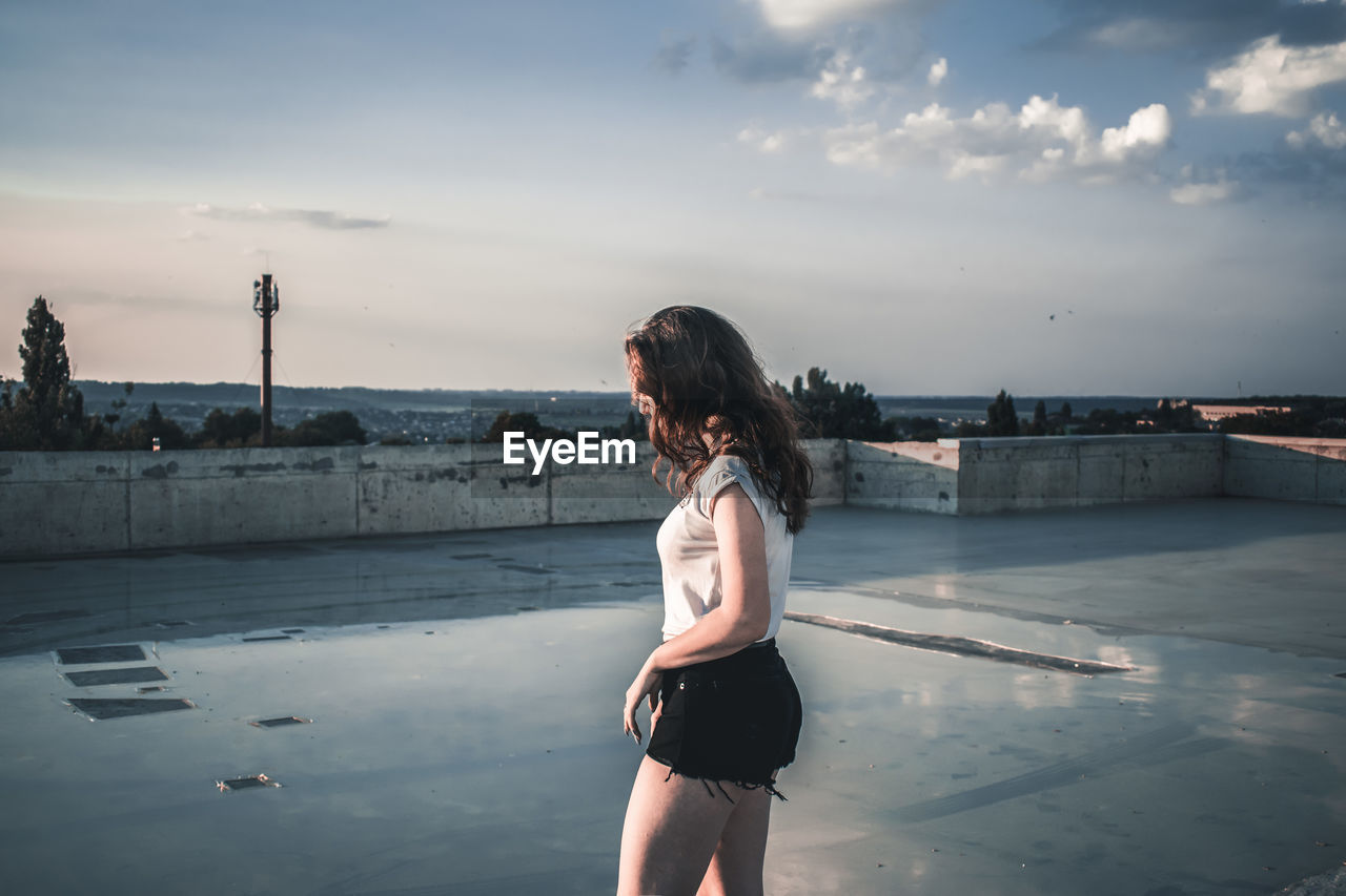 Woman standing on terrace against sky
