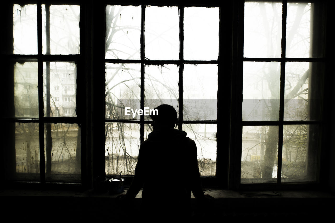 Silhouette Person Looking Through Window