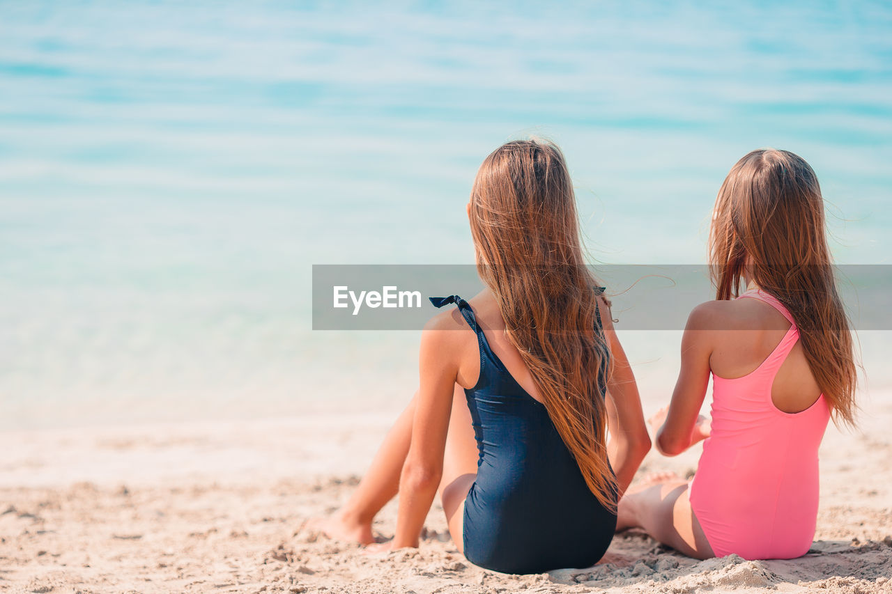 Rear view of sisters sitting on beach