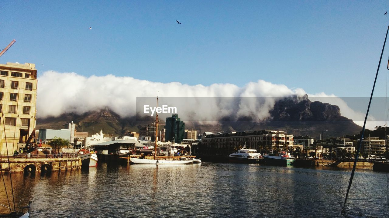 Scenic view of table mountain by lake against clear sky in city