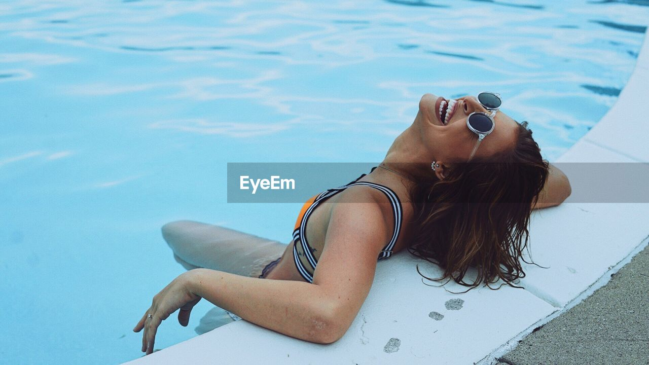 High Angle View Of Young Woman Enjoying In Swimming Pool
