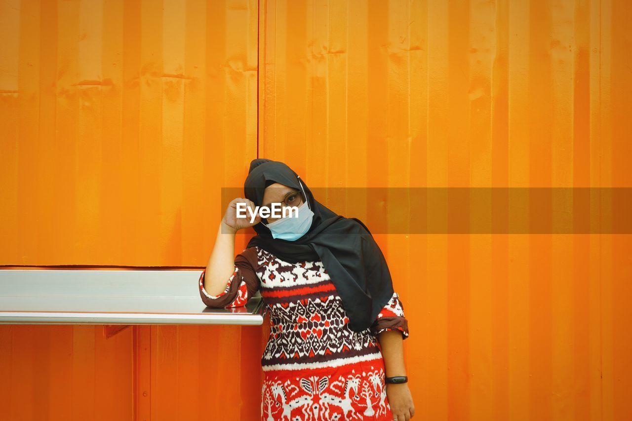 Portrait of woman wearing mask standing against orange wall