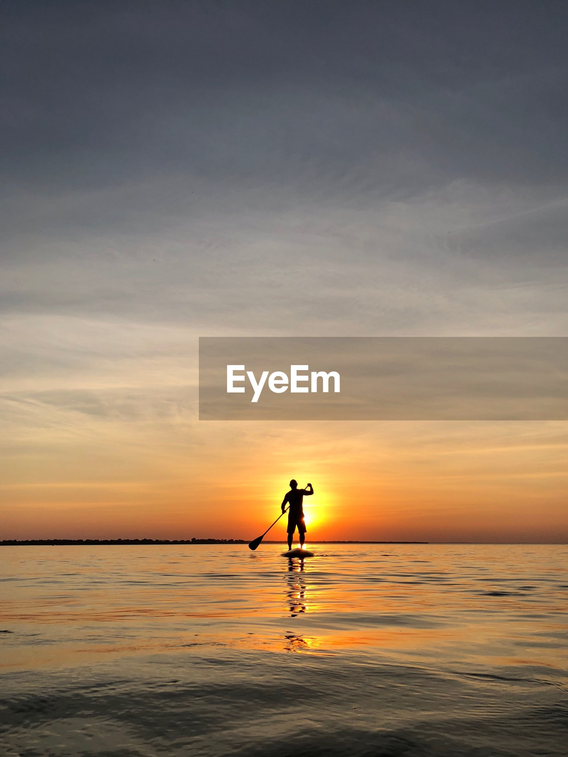 Silhouette of man paddleboarding on sea against sky during sunset