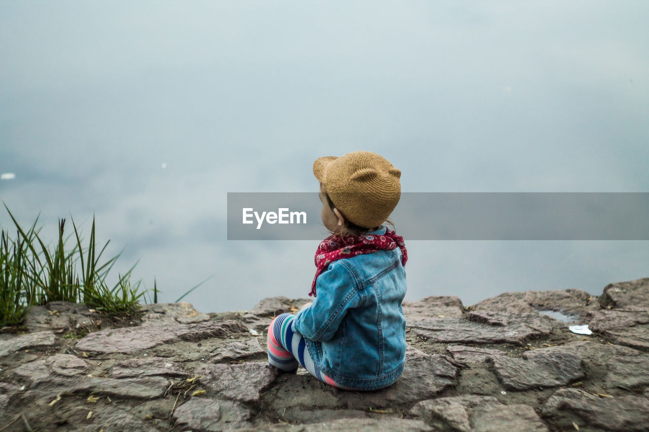 Rear View Of Boy Sitting On Rock Against Cloudy Sky