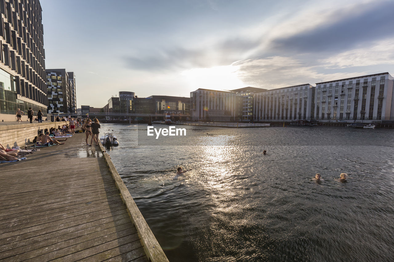 architecture, built structure, sky, building exterior, water, city, nature, cloud - sky, building, group of people, river, bridge, day, outdoors, incidental people, transportation, sunlight, office, real people, office building exterior, cityscape, skyscraper
