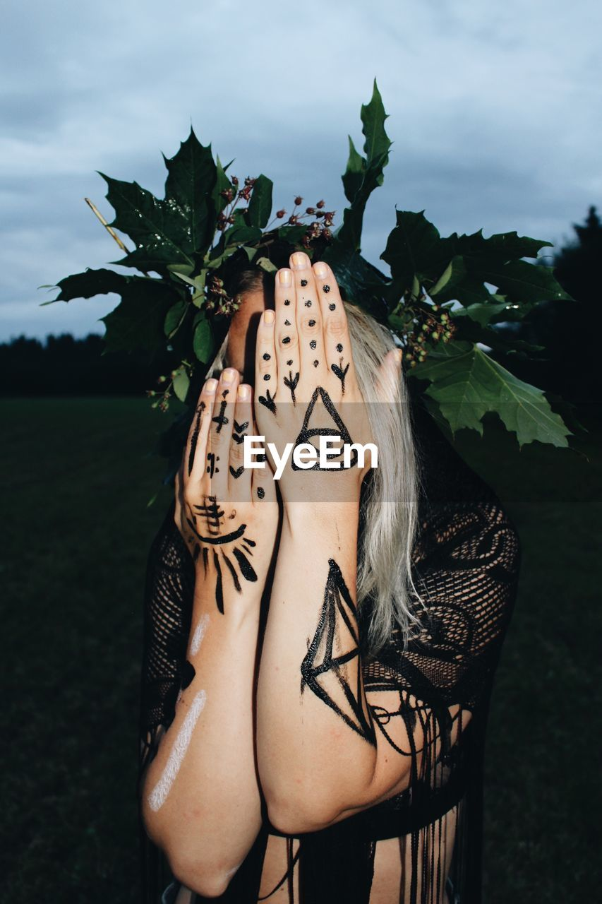 Close-Up Of Woman Covering Face With Tattoos On Hands While Standing Outdoors
