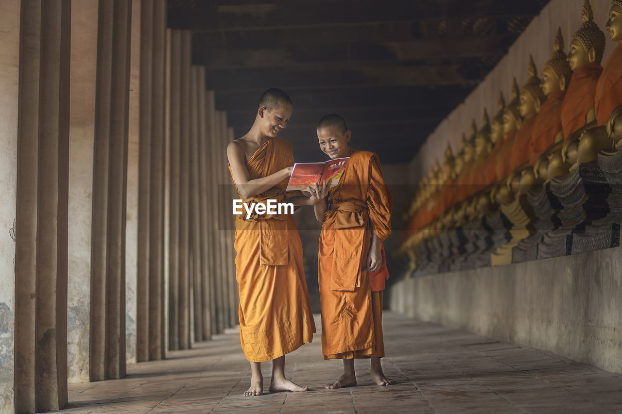 Monks Smiling While Reading Book In Corridor