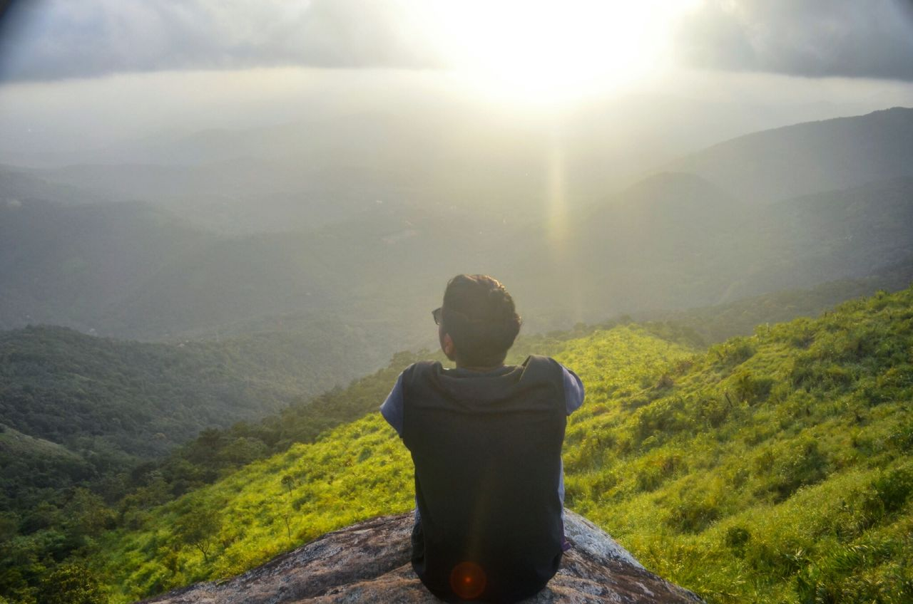 Rear view of hiker looking at mountains against sky