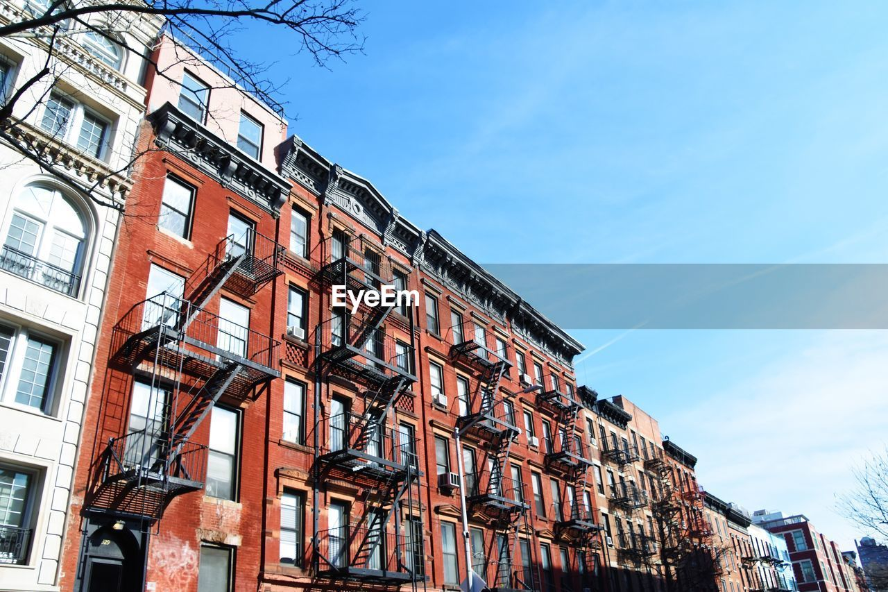 Row of traditional red brick buildings with fire escapes in east village, manhattan, new york city