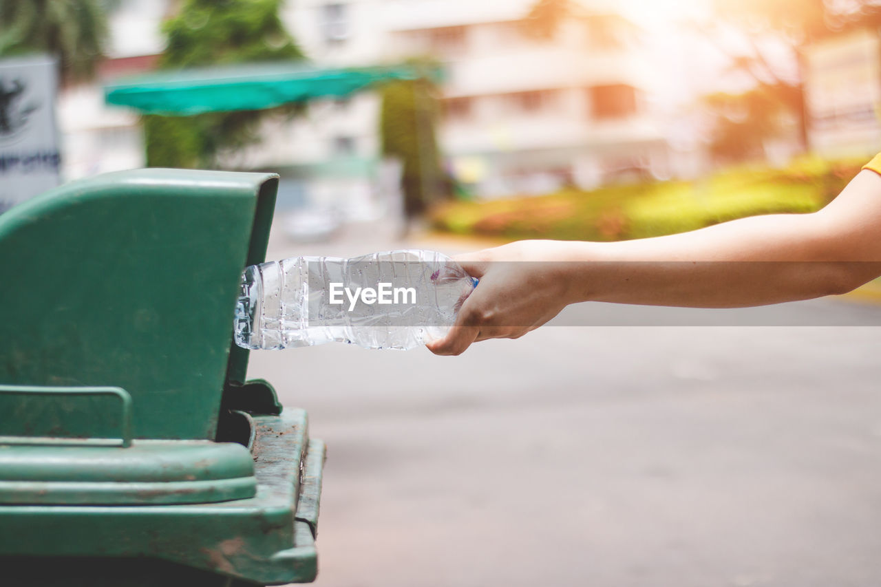 Cropped hand throwing bottle in garbage can