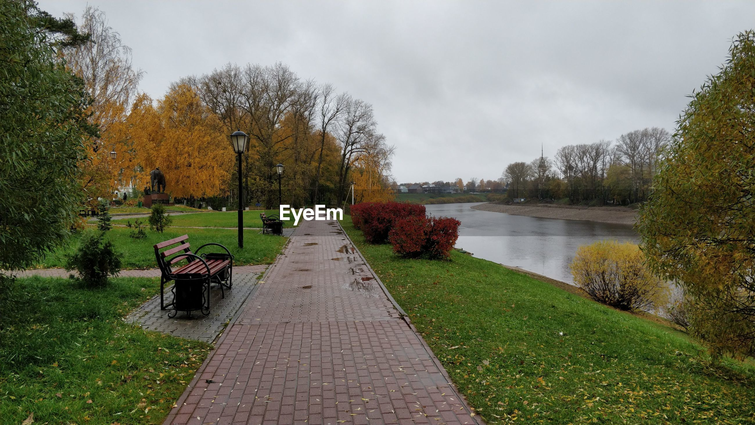 Park bench by lake against sky during autumn