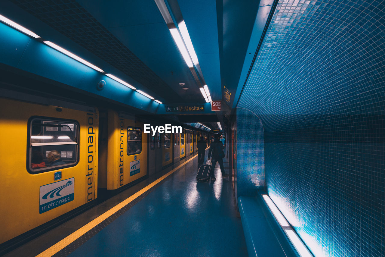 transportation, architecture, illuminated, public transportation, mode of transportation, indoors, travel, men, train, train - vehicle, rail transportation, real people, motion, subway station, people, built structure, subway, ceiling, lifestyles, group of people, subway train, modern