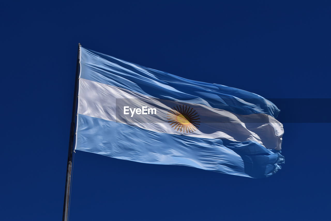 Low Angle View Of Argentinean Flag Against Blue Sky