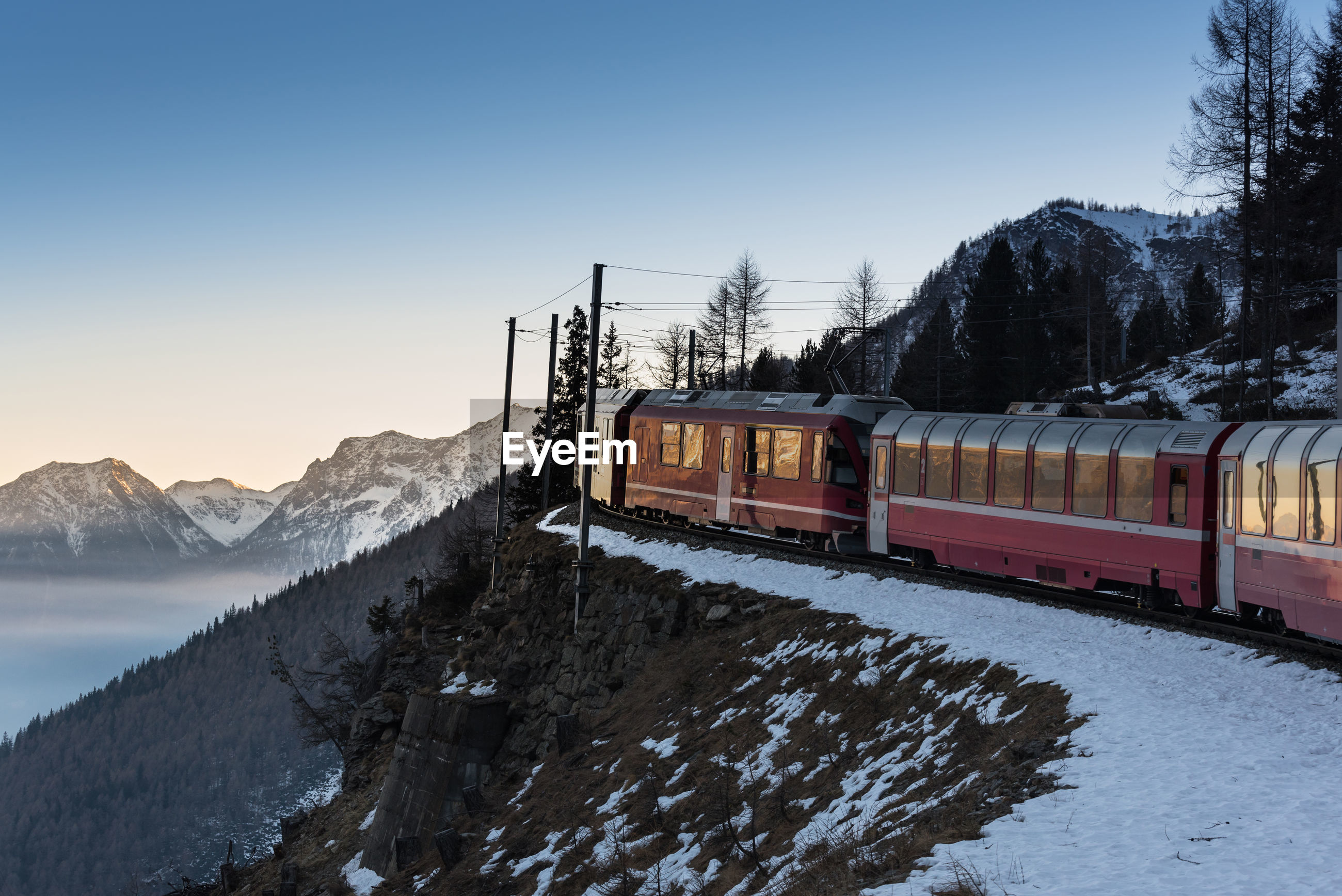 Train on mountains against clear sky during winter