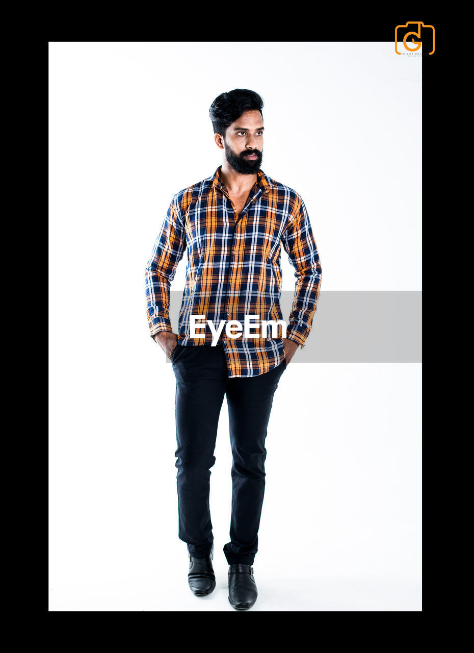 studio shot, checked pattern, one person, full length, standing, front view, white background, casual clothing, looking at camera, young adult, real people, portrait, one young man only, one man only, day, adult, people, adults only