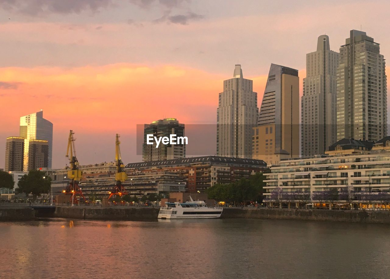architecture, building exterior, built structure, skyscraper, waterfront, city, sky, water, modern, cityscape, sunset, urban skyline, river, no people, travel destinations, outdoors, tall, nautical vessel, day