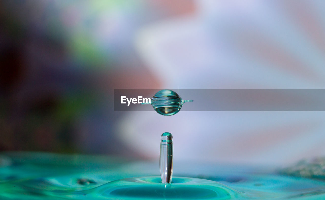 Close-Up Of Blue Drop Falling In Water Against Gray Background