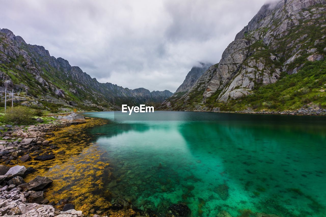 mountain, water, beauty in nature, scenics - nature, tranquil scene, sky, tranquility, rock, nature, non-urban scene, cloud - sky, lake, mountain range, rock - object, idyllic, no people, day, solid, physical geography, outdoors, turquoise colored, formation, lagoon