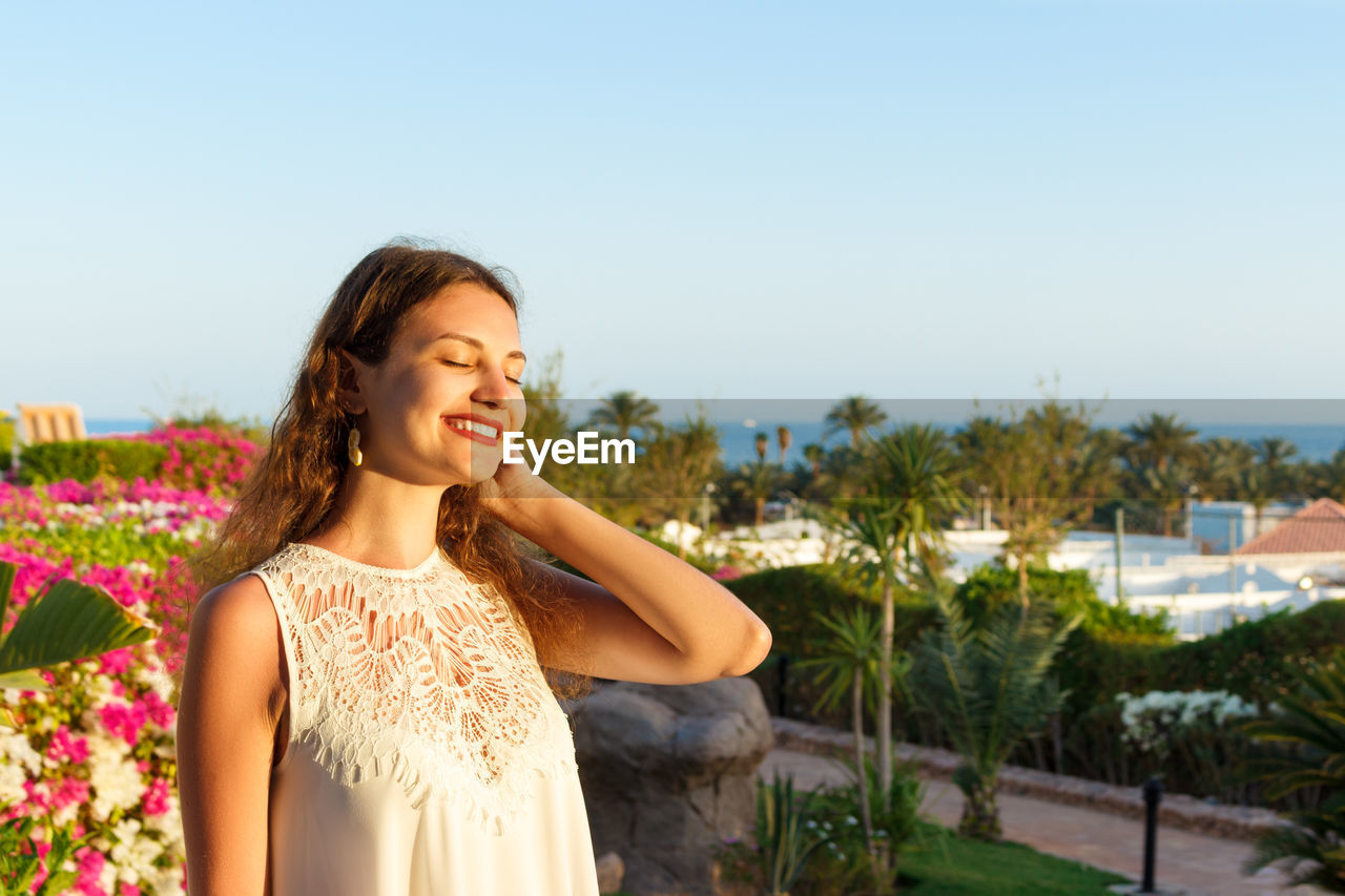Smiling young woman with eyes closed standing against sky