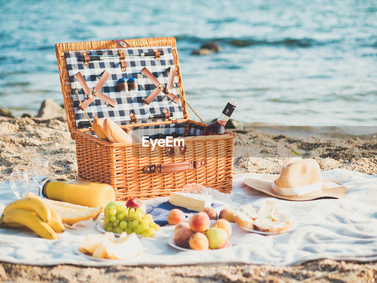 Various Fruits In Basket On Picnic Blanket At Shore