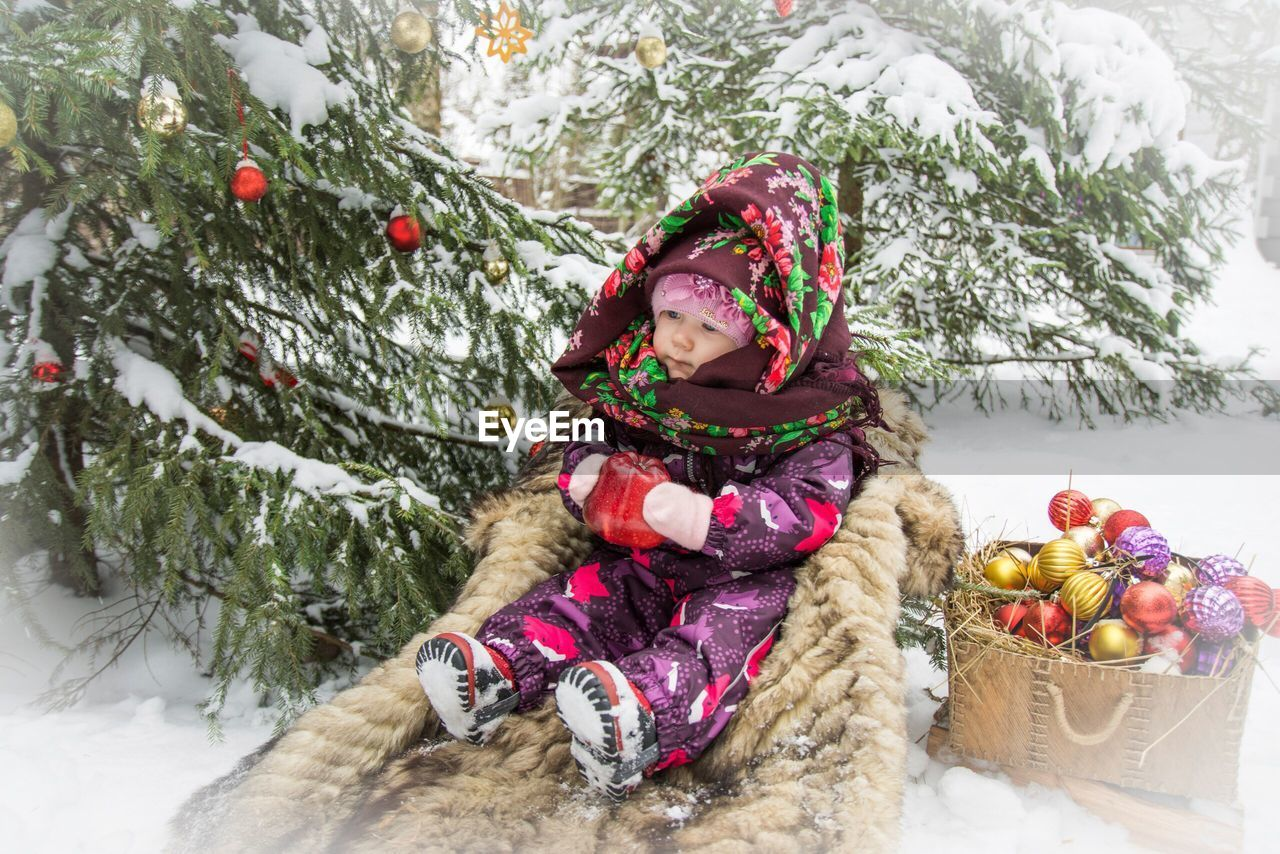 High angle view of cute girl sitting by christmas tree during winter