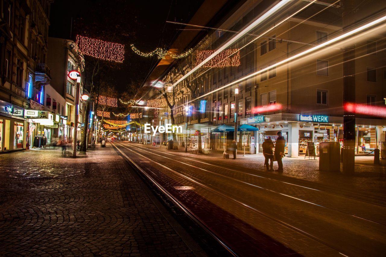 RAILROAD TRACKS IN CITY AT NIGHT