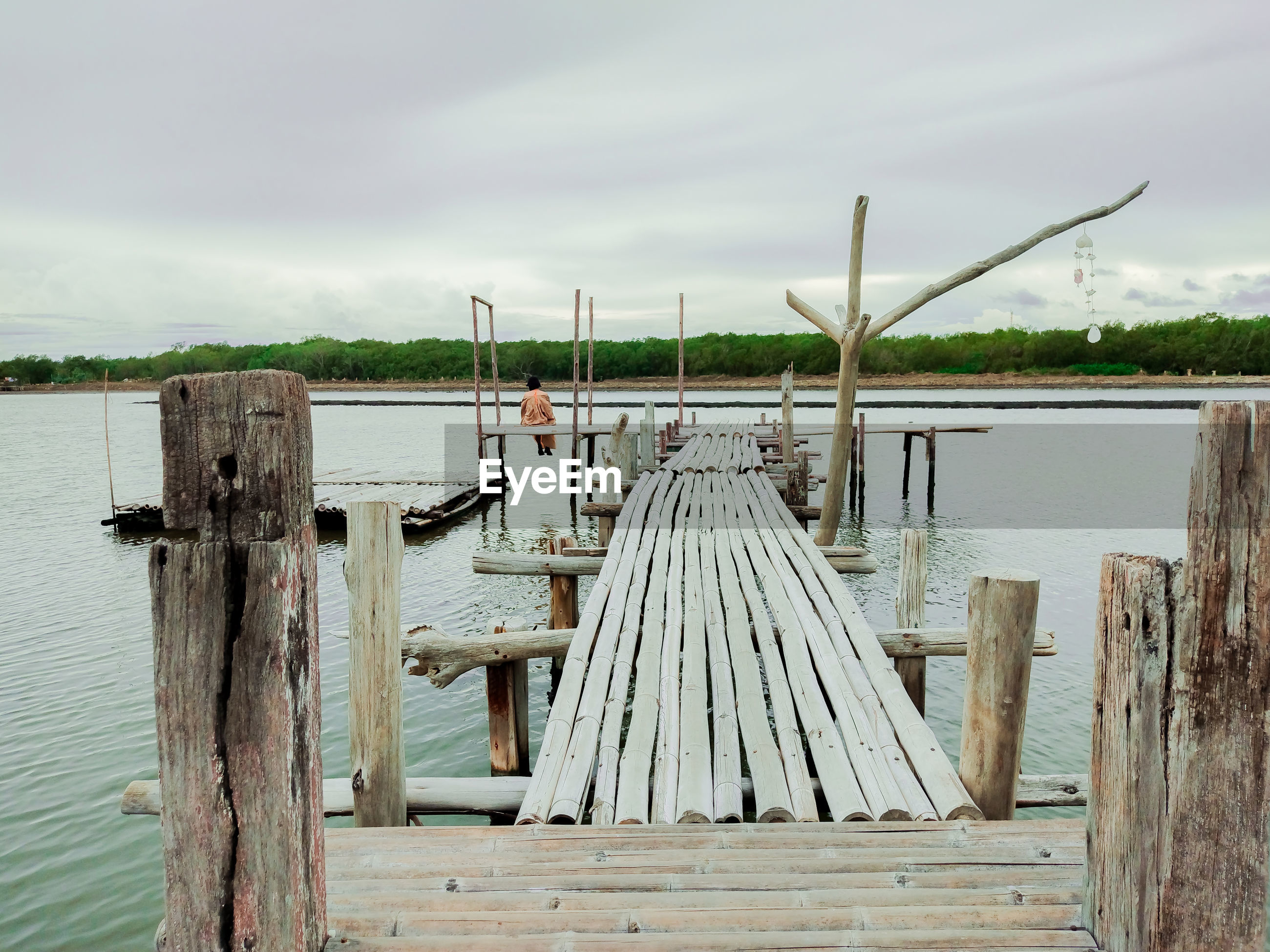 A woman sitting at a wooden bridge by the sea
