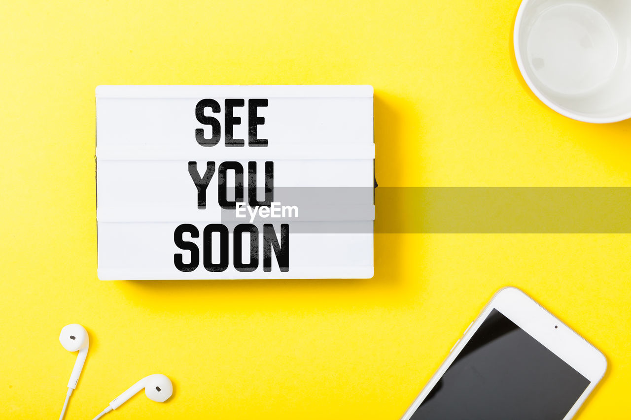 yellow, communication, text, western script, no people, indoors, close-up, capital letter, sign, yellow background, wireless technology, technology, note, studio shot, information, smart phone, still life, table, paper, black color, message