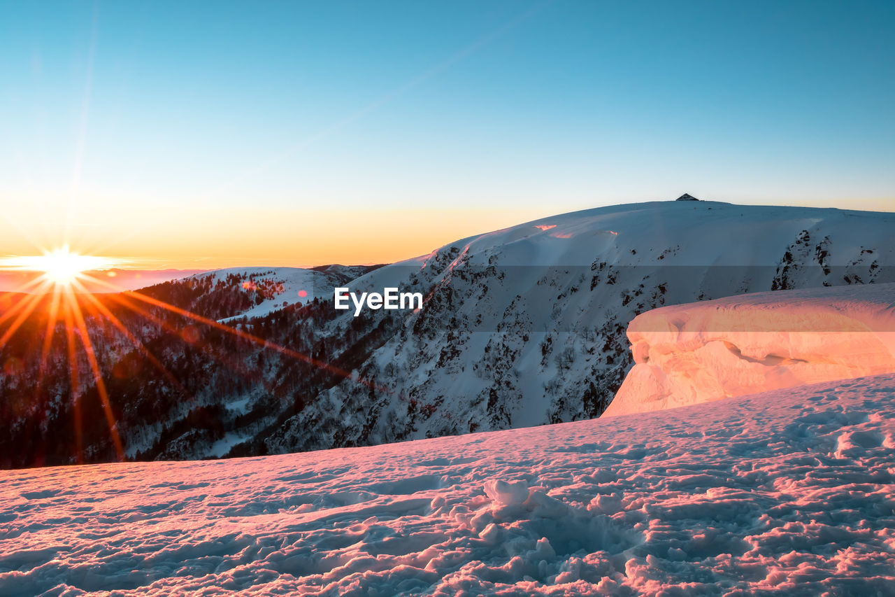winter, cold temperature, snow, sky, beauty in nature, scenics - nature, sunset, tranquility, tranquil scene, sun, mountain, environment, sunlight, nature, non-urban scene, landscape, sunbeam, no people, covering, lens flare, snowcapped mountain, bright, mountain peak