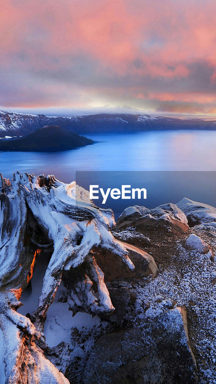 Scenic View Of Snowcapped Mountains And Sea Against Cloudy Sky During Sunset