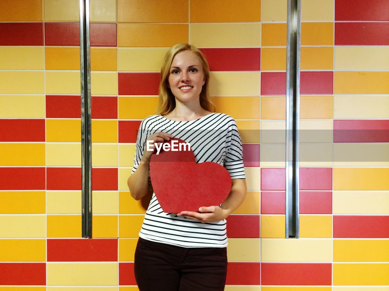 Portrait of smiling young woman holding red heart shape while standing against wall