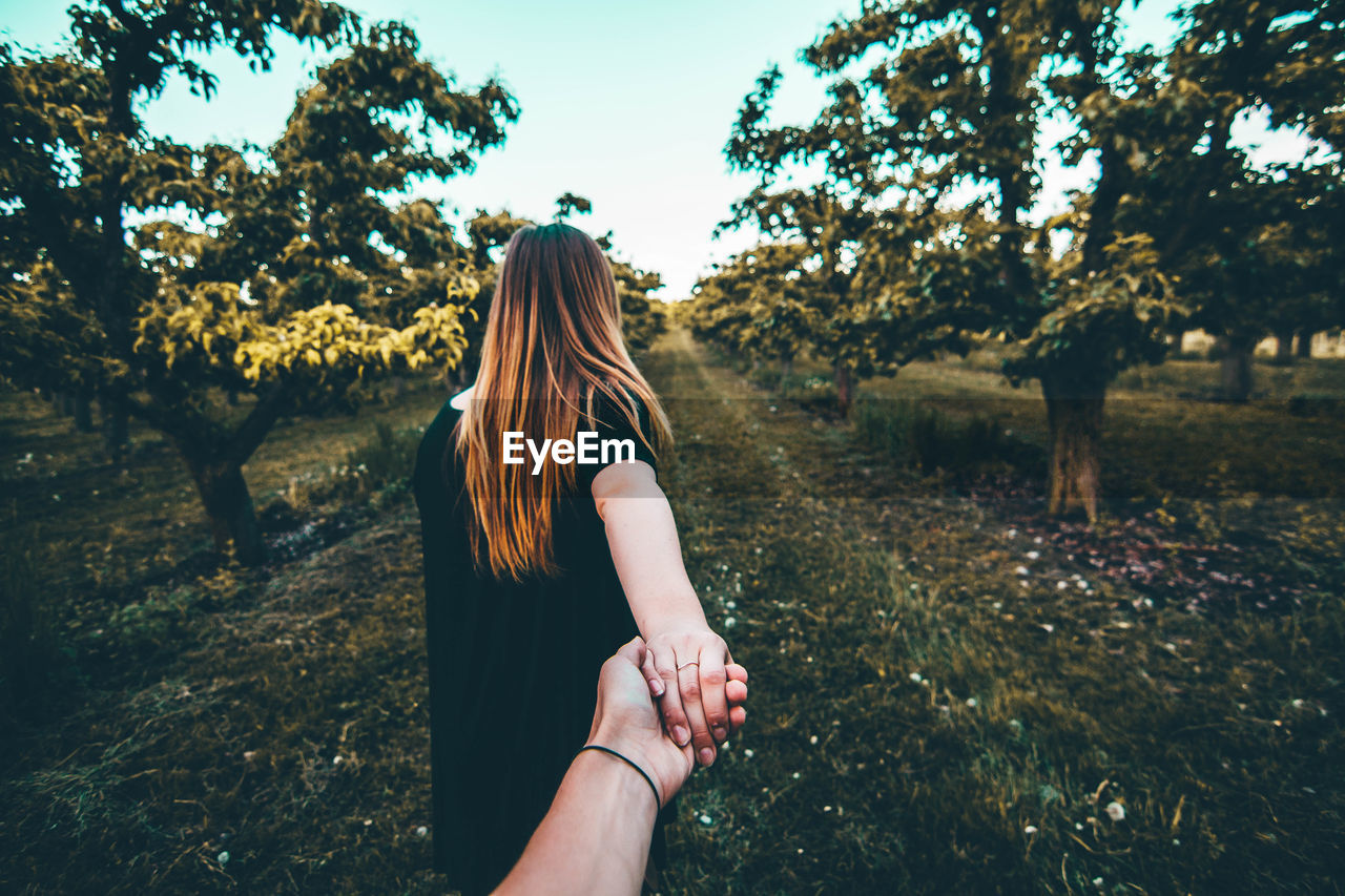 Cropped hand of man holding girlfriend hand on grassy field