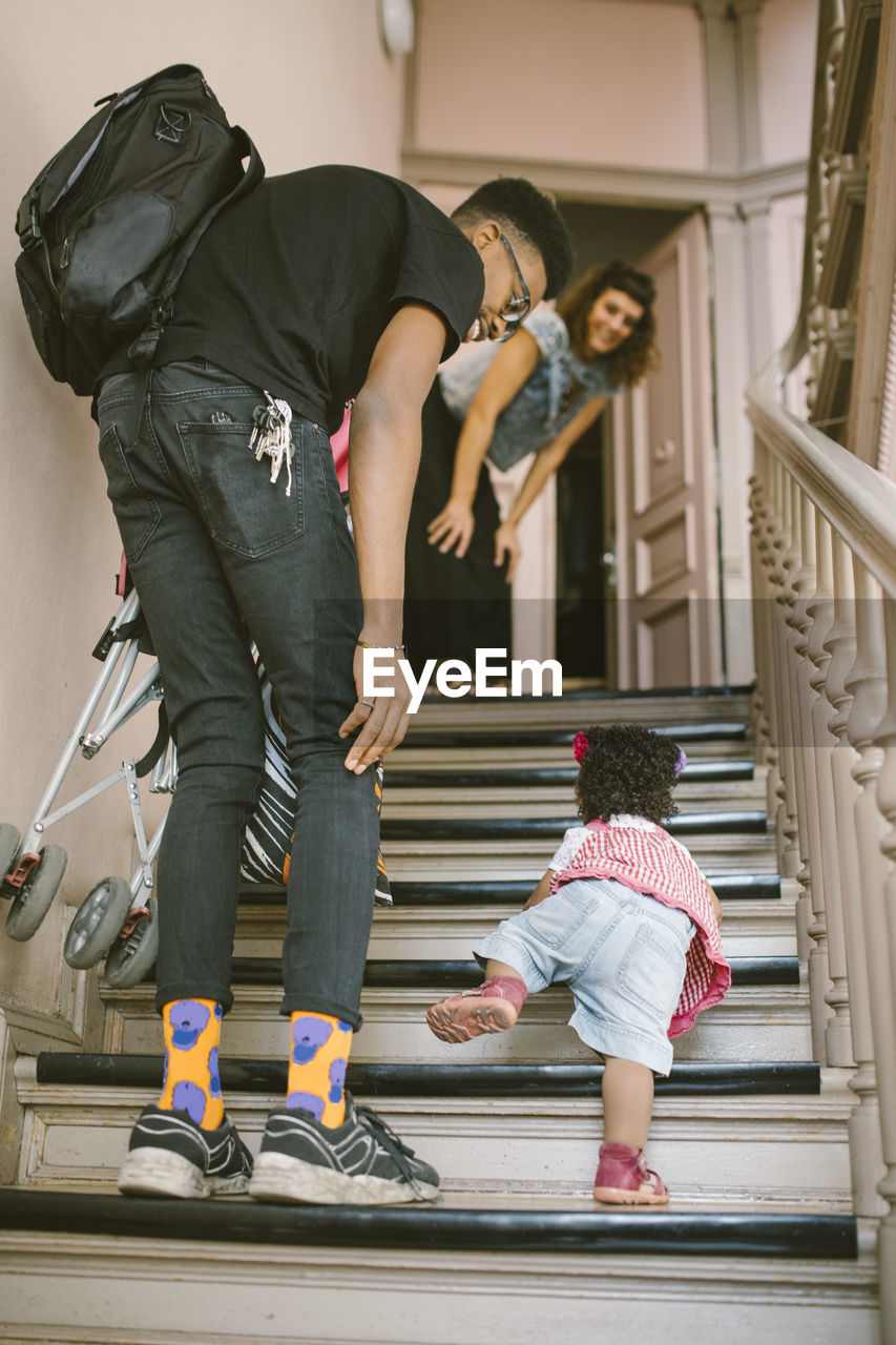 full length, real people, togetherness, two people, staircase, women, architecture, family, bonding, females, casual clothing, lifestyles, childhood, adult, steps and staircases, people, men, love, child, daughter, positive emotion, sister