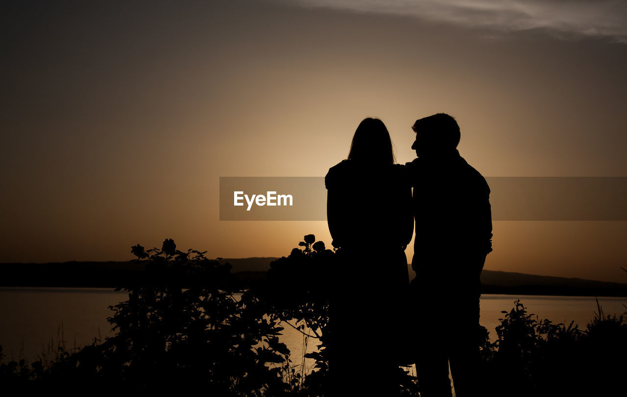 Rear view of silhouette couple overlooking calm lake