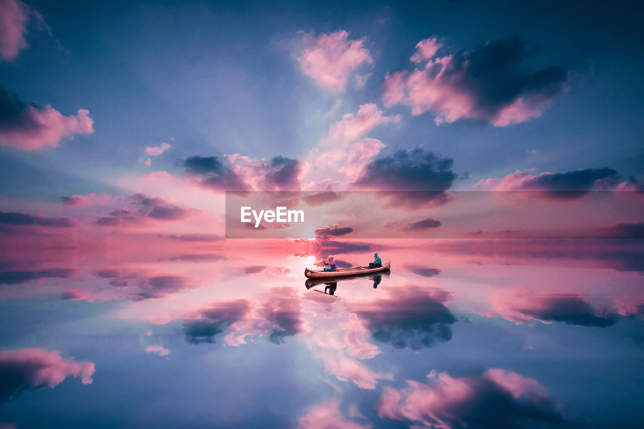 People sailing boat in calm river during sunset