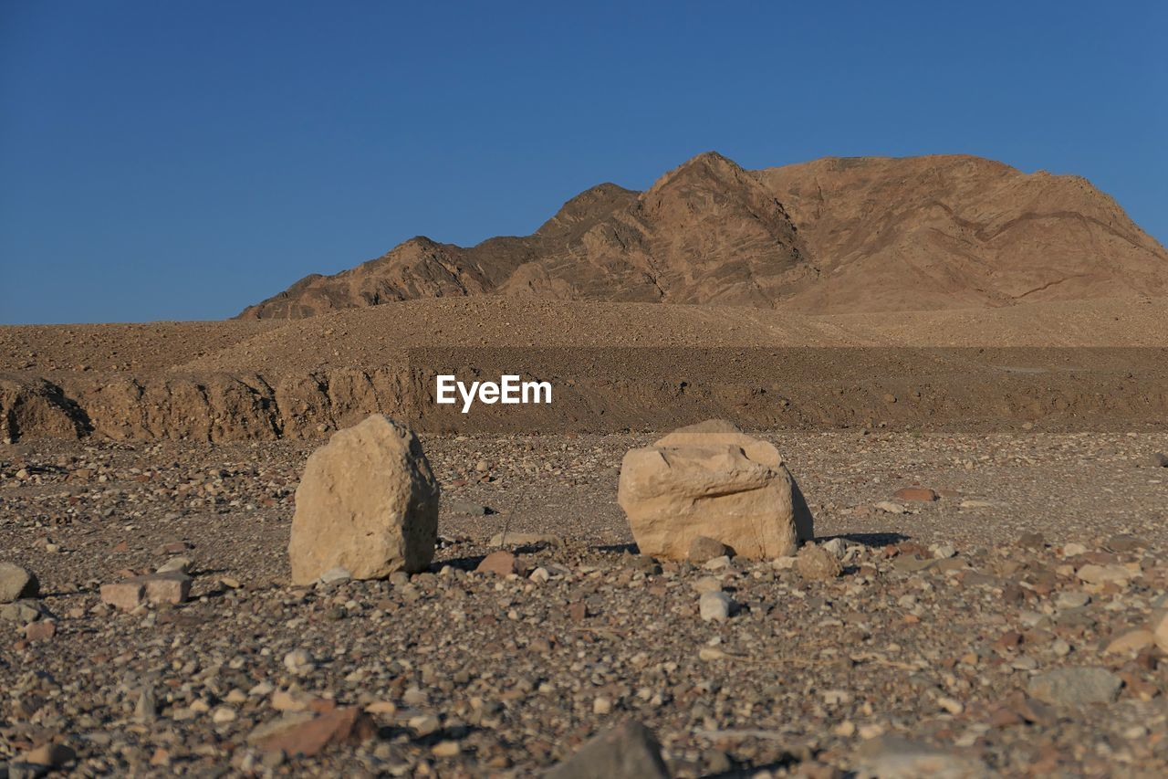 sky, landscape, land, clear sky, scenics - nature, desert, environment, nature, rock, tranquil scene, tranquility, solid, blue, climate, mountain, rock - object, beauty in nature, arid climate, no people, non-urban scene, mountain range, outdoors, formation, ancient civilization