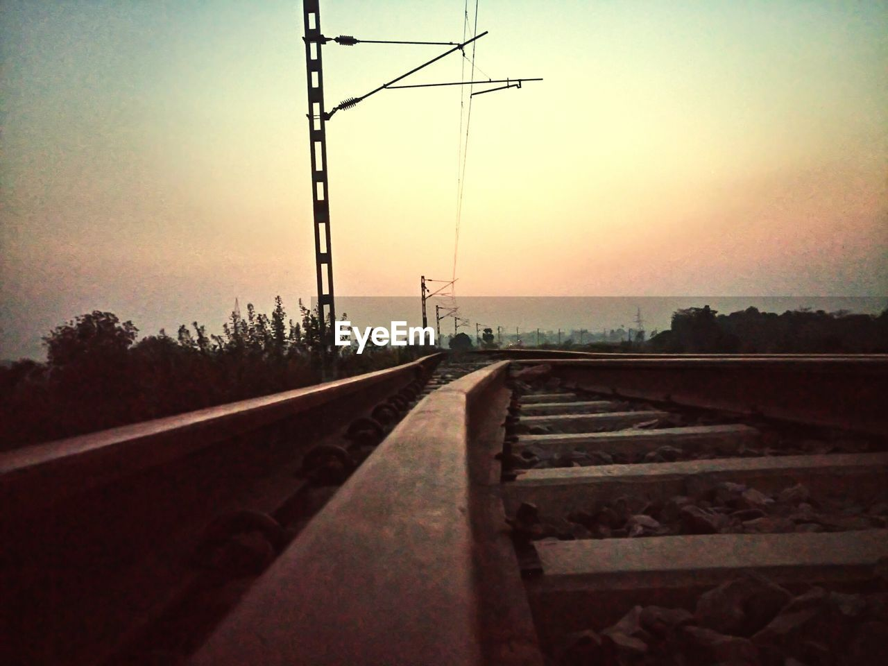 sky, transportation, rail transportation, track, sunset, railroad track, nature, direction, no people, the way forward, diminishing perspective, connection, mode of transportation, electricity pylon, electricity, vanishing point, metal, outdoors, technology, tree, straight, power supply, surface level