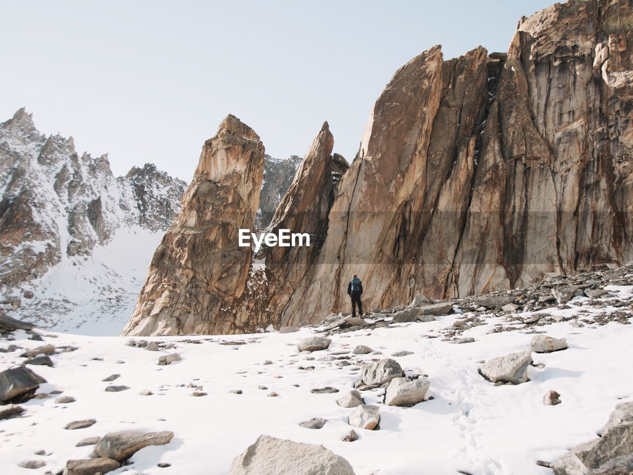 Rear view of man standing against rock formations during winter