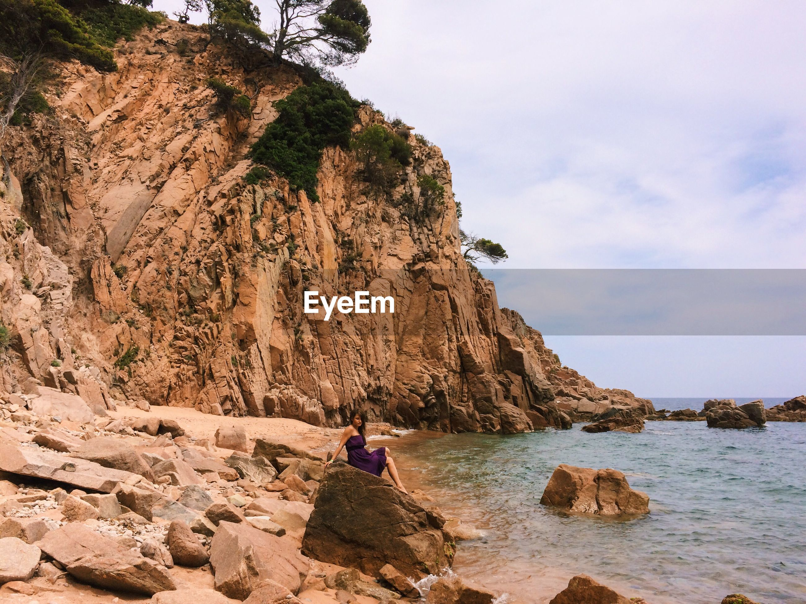 Woman sitting on rock at seaside against cloudy sky