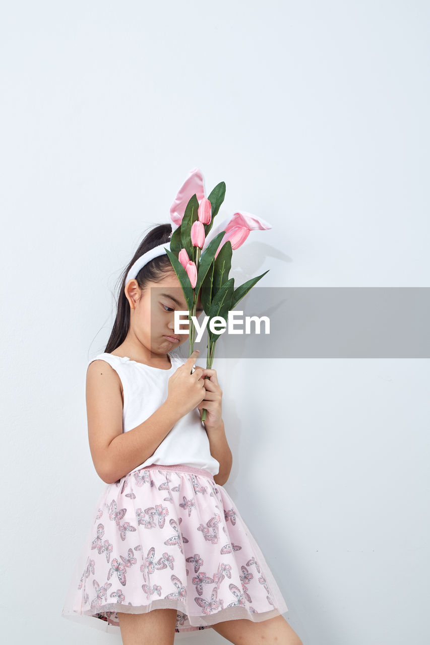 Thoughtful girl with pink flowers standing against wall