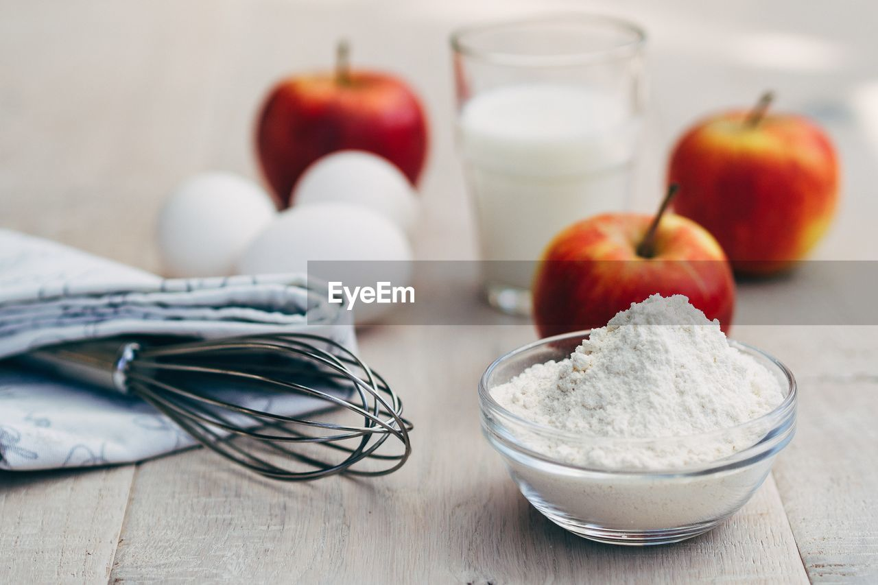 Close-up of wire whisk with apples and flour