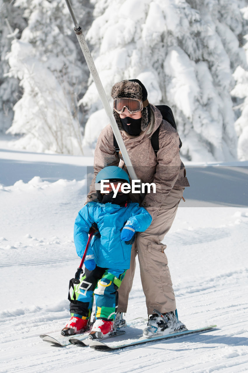 Mature Woman Teaching Son Skiing On Snow Covered Field