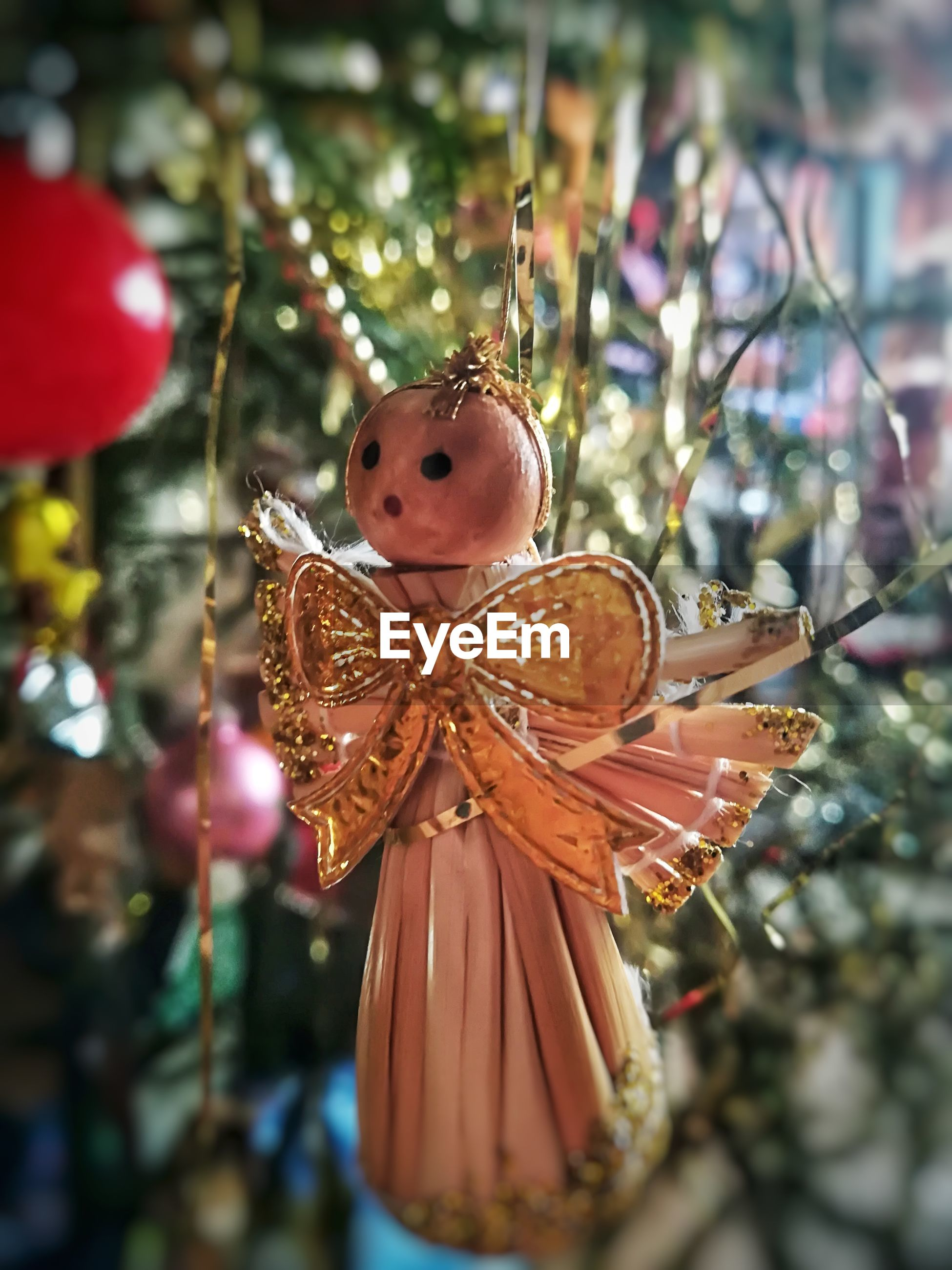 Close-up of angel figurine hanging on christmas tree