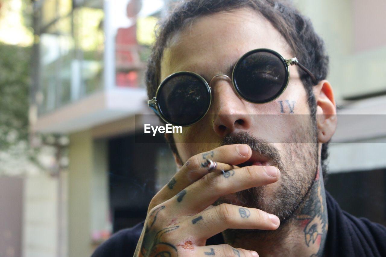 Close-Up Portrait Of Man Wearing Sunglasses Smoking Cigarette