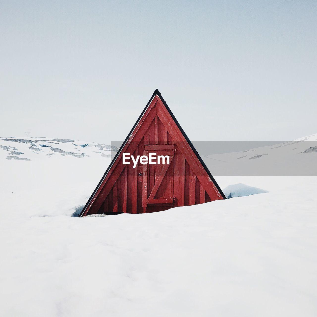 Barn on snow covered field against sky