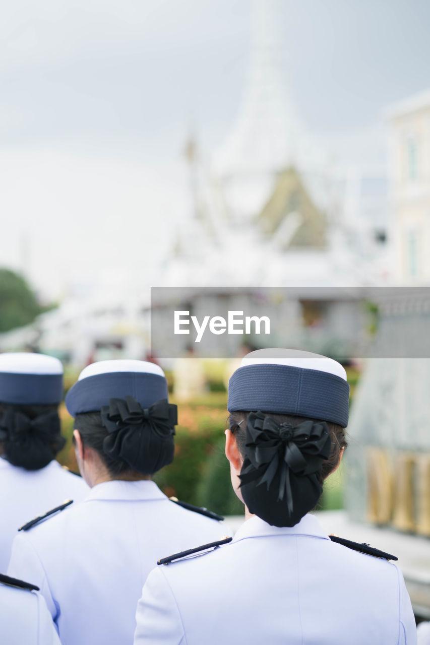 Rear view of women wearing uniform in city