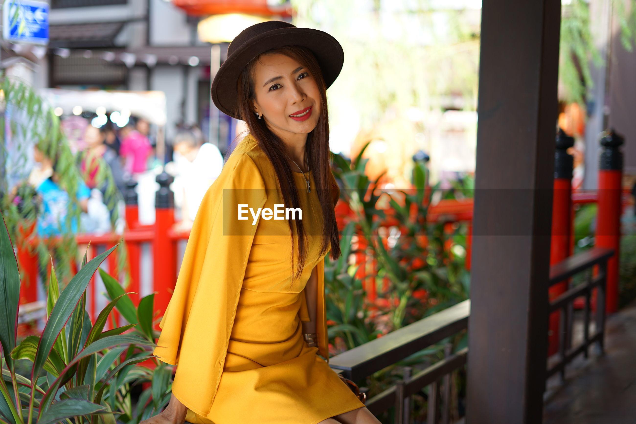 Portrait of woman in yellow dress sitting on railing