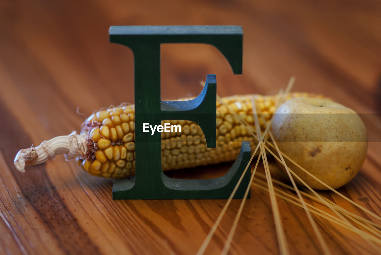 Close-Up Of Letter E By Corn Pear On Table
