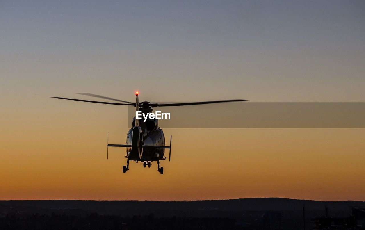 Helicopter Flying Above Landscape During Sunset